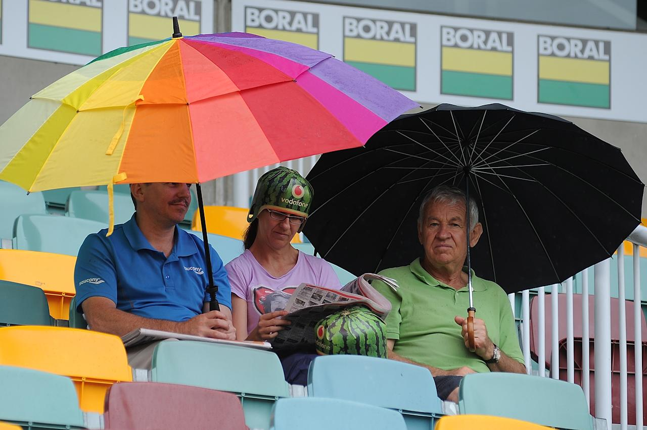 BRISBANE, AUSTRALIA - NOVEMBER 10:  Spectators sit in the stands as rain delays the start of play on day two of the First Test match between Australia and South Africa at The Gabba on November 10, 2012 in Brisbane, Australia.  (Photo by Matt Roberts/Getty Images)