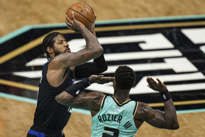 Los Angeles Clippers guard Paul George shoots the ball over Charlotte Hornets guard Terry Rozier during the first half of an NBA basketball game in Charlotte, N.C., Thursday, May 13, 2021. (AP Photo/Jacob Kupferman)