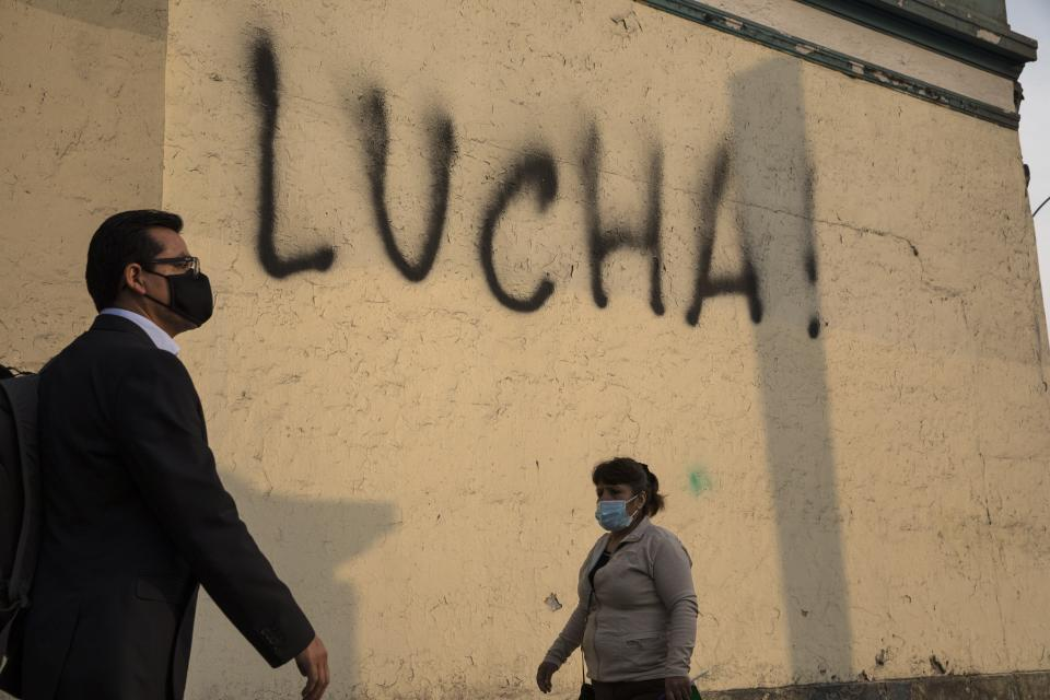 Pedestrians walk past a wall spray-painted by an anti-government protester with the Spanish word for fight, just a block from the Justice Palace where people who are refusing to recognize Peru's new government gathered to protest, in Lima, Wednesday, Nov. 11, 2020. On Tuesday, Peru swore in former congressional leader Manuel Merino as president, after the legislature booted President Martin Vizcarra from office on Monday. (AP Photo/Rodrigo Abd)