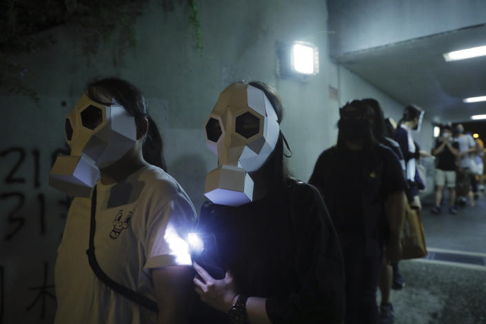 Protesters wear paper face masks and hold up their mobile phone lights in Hong Kong, Friday, Oct. 18, 2019. Hong Kong pro-democracy protesters are donning cartoon/superhero masks as they formed a human chain across the semiautonomous Chinese city, in defiance of a government ban on face coverings. (AP Photo/Kin Cheung)
