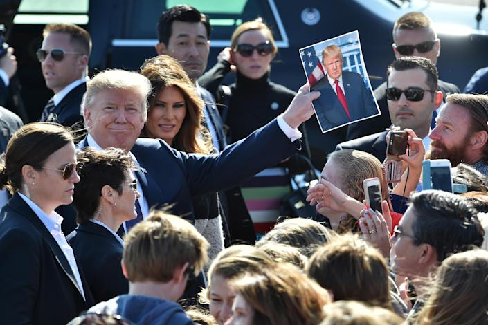 <p>President Donald Trump, third left, holds a photograph of himself while U.S. First Lady Melania Trump, fourth left, looks on as they greet attendees after arriving at U.S. Yokota Air Base in Fussa, Tokyo Metropolis, Japan, on Sunday, Nov. 5, 2017. (Photo: Kazuhiro Nogi/Pool via Bloomberg via Getty Images) </p>