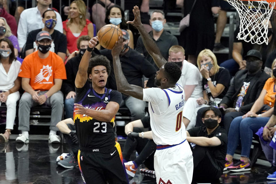 Phoenix Suns forward Cameron Johnson (23) passes around Denver Nuggets forward JaMychal Green (0) during the first half of Game 2 of an NBA basketball second-round playoff series, Wednesday, June 9, 2021, in Phoenix. (AP Photo/Matt York)