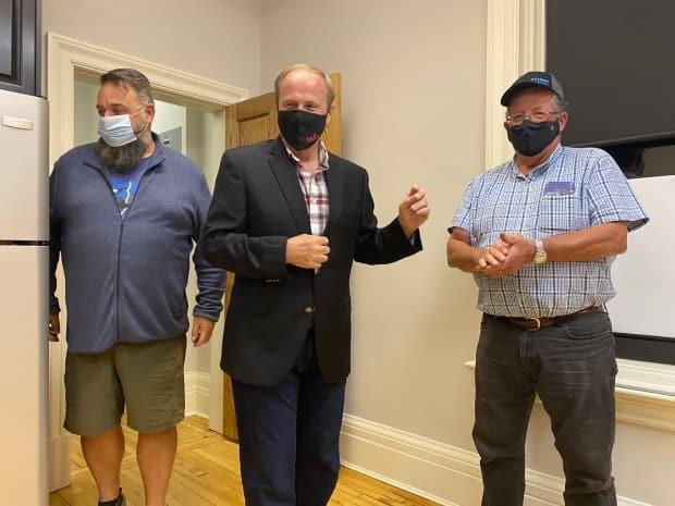 Robert Morrissey is joined by provincial Liberal MLA Hal Perry and Frank Martin in Tignish Monday night. (Wayne Thibodeau/CBC - image credit)