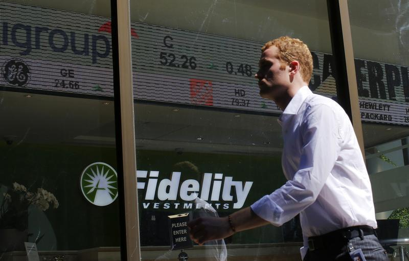 A pedestrian walks past a stock ticker at a Fidelity Investments office in Boston