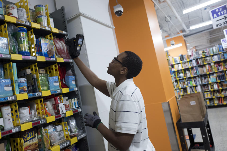 FILE- In this Dec. 20, 2017, file photo, a clerk reaches to pick an item for a customer order at the Amazon Prime warehouse in New York. Amazon is boosting its minimum wage for all U.S. workers to $15 per hour starting next month. The company said Tuesday, Oct. 2, 2018, that the wage hike will benefit more than 350,000 workers, which includes full-time, part-time, temporary and seasonal positions. (AP Photo/Mark Lennihan, File)