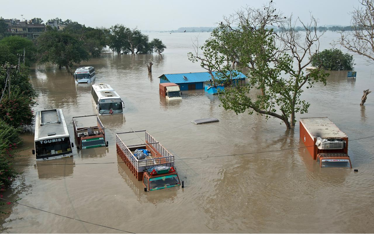 Buses and trucks are submerged in the rising waters of the Yamuna River near the Tibetan market in New Delhi on June 19, 2013.  Military helicopters dropped emergency supplies June 19 to thousands of tourists and pilgrims stranded by flash floods that tore through towns and temples in northern India, killing at least 138 people, officials said.   AFP PHOTO/Prakash SINGH