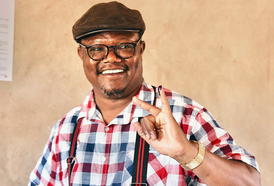Chadema Presidential Candidate Tundu Lissu smiles as he shows his finger marked with ink after casting his vote at Ntewa Primary School's polling station in Ikungi town Singida region, Tanzania, Wednesday. Oct.28, 2020. Opposition challenger Lissu has urged people to go into the streets to protest if election results are announced Thursday without being counted properly. (AP Photo)
