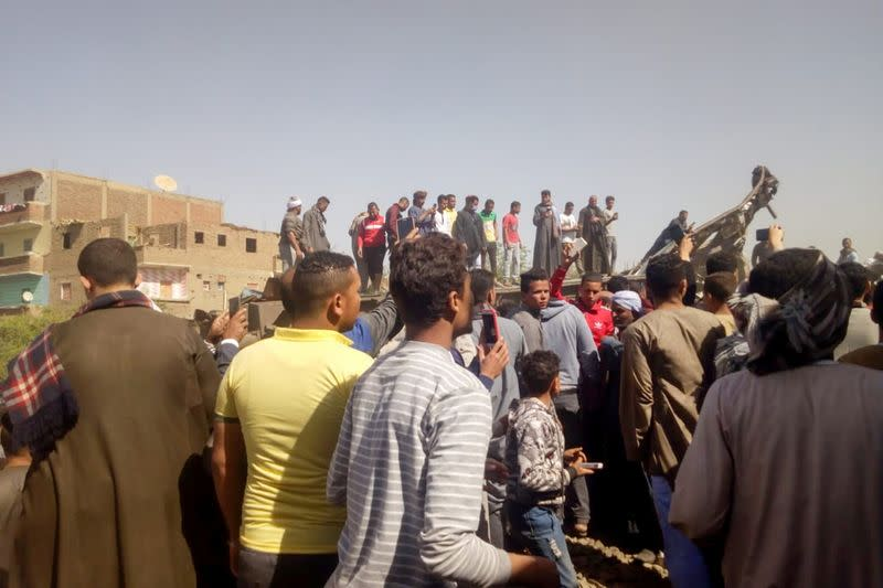 People inspect the damage after two trains have collided near the city of Sohag