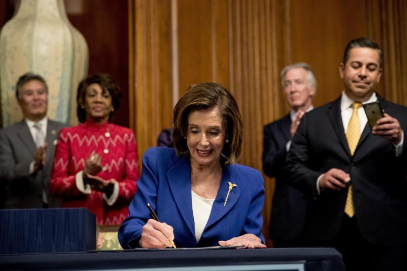 House Speaker Nancy Pelosi of Calif., accompanied by bipartisan legislators, signs the Coronavirus Aid, Relief, and Economic Security (CARES) Act after it passed in the House on Capitol Hill, Friday, March 27, 2020, in Washington. The $2.2 trillion package will head to head to President Donald Trump for his signature. (AP Photo/Andrew Harnik)