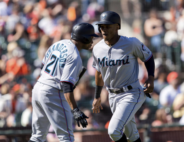 Miami Marlins' Magneuris Sierra, right, celebrates with Curtis Granderson (21) after he scores a run against the San Francisco Giants in the seventh inning of a baseball game in San Francisco, Sunday, Sept. 15, 2019. (AP Photo/John Hefti)