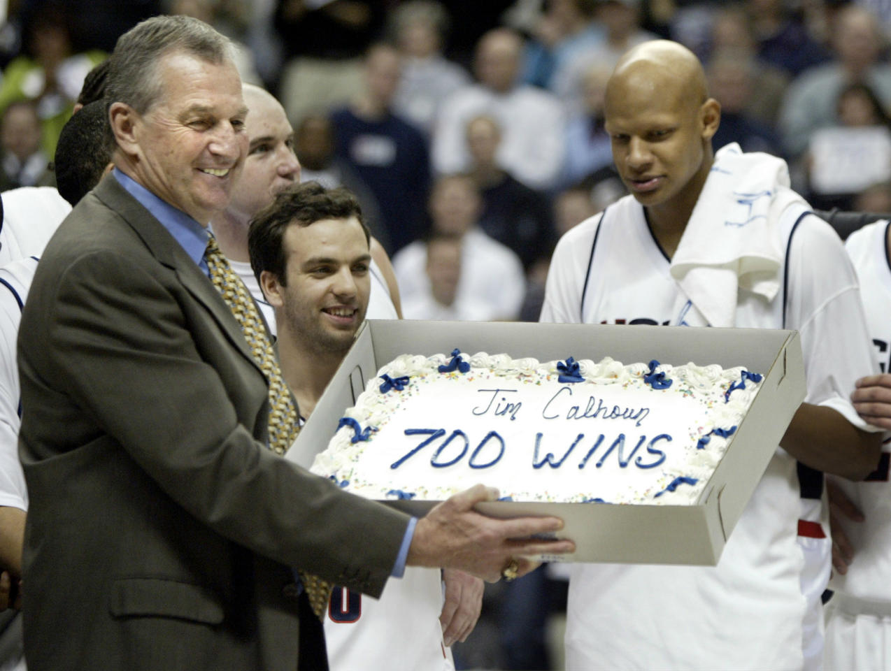 University of Connecticut basketball head coach Jim Calhoun (L) holds up a cake from his players after he achieved his 700th career win with an 83-64 win over Georgetown in Storrs, Connecticut March 2, 2005. With Calhoun are Sami Ameziane (C) and Chalie Villanueva. REUTERS/Brian Snyder  BS