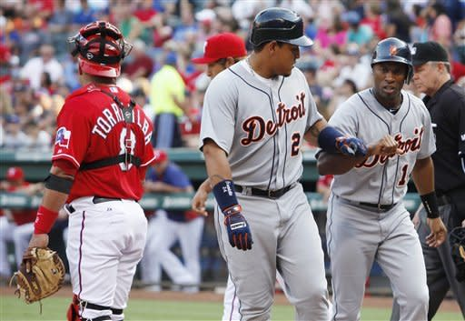 Detroit Tigers Miguel Cabrera, center, and Austin Jackson celebrate after scoring on a double by Prince Fielder, as Texas Rangers catcher Yorvit Torrealba (8) talks to pitcher Yu Darvish, beind Cabrera, during the first inning of a baseball game Tuesday, June 26, 2012, in Arlington, Texas. (AP Photo/Tim Sharp)