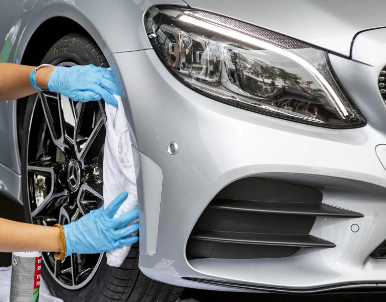 A woman cleans a Mercedes car at the IAA Auto Show in Frankfurt, Germany, Monday, Sept. 9, 2019. The IAA officially starts with media days on Tuesday and Wednesday. (AP Photo/Michael Probst)