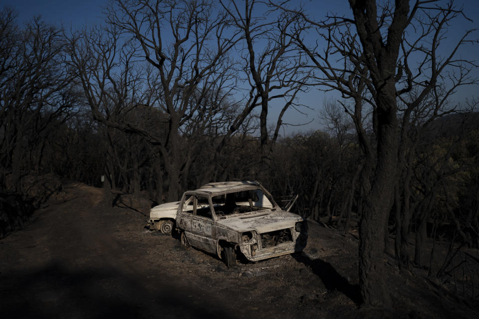 Cars burnt by wildfires are pictured in Val de Gilly, southern France, Thursday, Aug. 19, 2021. A fire that has ravaged forests near the French Riviera for four days is slowing down as winds and hot weather subside, but more than 1,100 firefighters were still struggling to get it under control Thursday, local authorities said. (AP Photo/Daniel Cole)