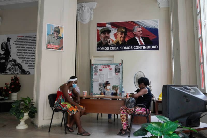 People sit under a poster with images of Fidel Castro, Raul Castro and Miguel Diaz-Canel in Havana