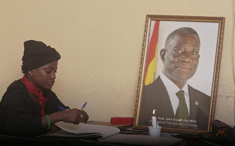 A woman signs a book of remembrance for the late Ghana President John Atta Mills, seen in the photo, at his party headquarters in Accra, Ghana, Wednesday, July 25, 2012. President John Atta Mills' election victory secured Ghana's reputation as one of the most mature democracies in West Africa, a position further solidified Tuesday when the vice president took over only hours after the 68-year-old president died five months before finishing his first term. (AP Photo/Christian Thompson)
