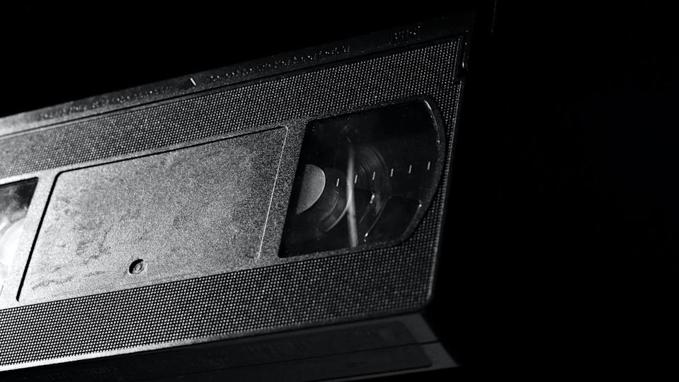 a photo of a plain black VHS tape from video store on a black background