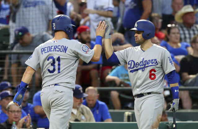 Los Angeles Dodgers' Joc Pederson (31) high fives Brian Dozier after scoring against the Texas Rangers in the third inning of a baseball game Tuesday, Aug. 28, 2018, in Arlington, Texas. (AP Photo/Richard W. Rodriguez)