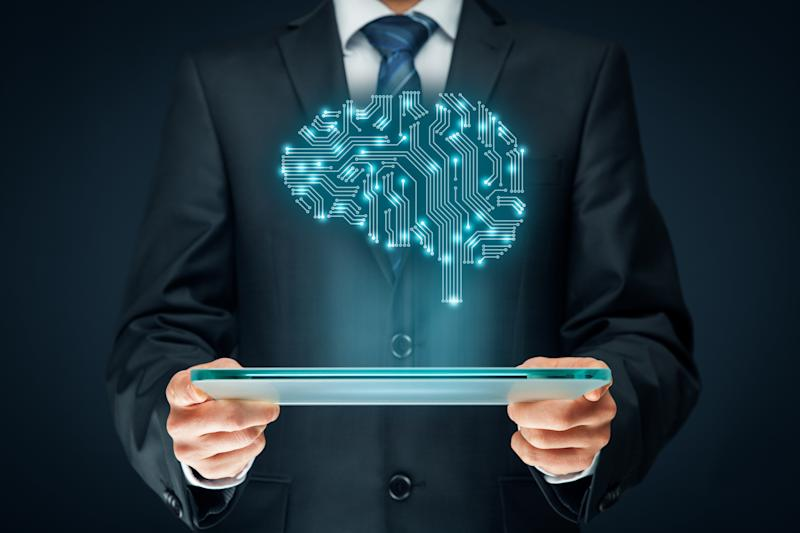 A man in a suit holding a tablet with an illustrated brain made of electrical connections hovering above it, illustrating artificial intelligence.