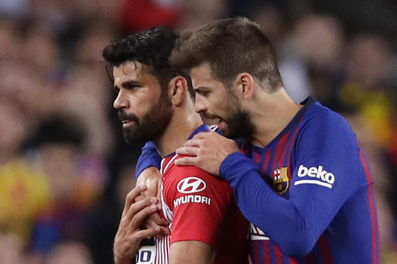 Barcelona's Gerald Pique, right, talks to Atletico forward Diego Costa who was sent off with a red card for insulting referee Jesus Gil Manzano during a Spanish La Liga soccer match between FC Barcelona and Atletico Madrid at the Camp Nou stadium in Barcelona, Spain, Saturday April 6, 2019. (AP Photo/Manu Fernandez)