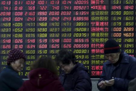 Investors stand in front of an electronic board showing stock information on the first trading day after the week-long Lunar New Year holiday at a brokerage house in Shanghai