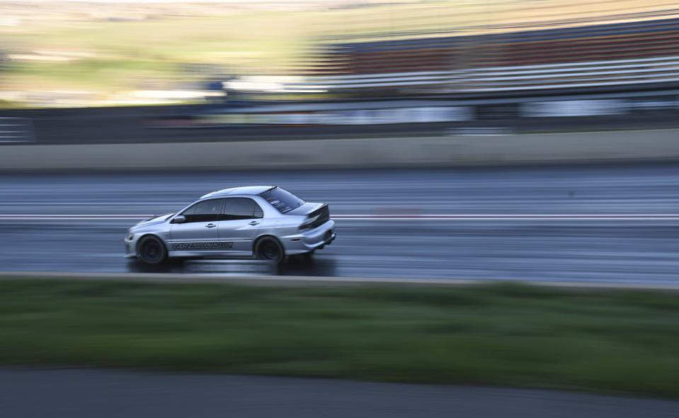 """A car races down the quarter-mile track at Bandimere Speedway west of Denver on May 5, 2021. The Colorado State Patrol runs a program called """"Take it to the Track"""" in hopes of luring racers away from public areas to a safer and more controlled environment, even allowing participants to race a trooper driving a patrol car. The program's goals have gained new importance and urgency this year as illegal street racing has increased amid the coronavirus pandemic. (AP Photo/Thomas Peipert)"""