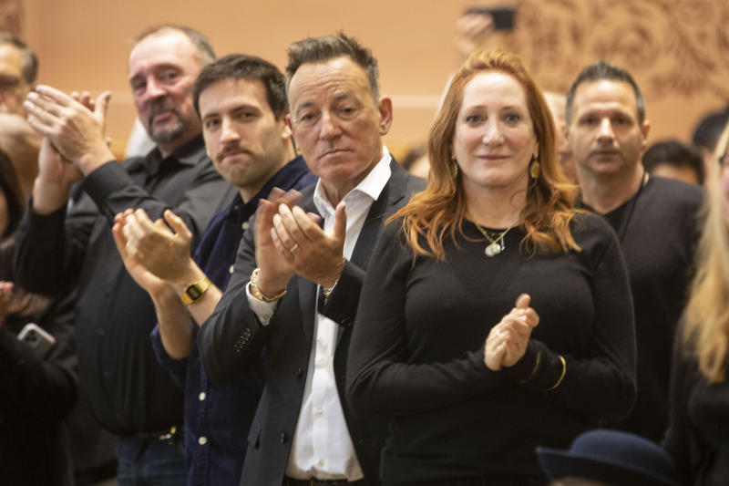 In this photo provided by the Jersey City Mayor's Office, Bruce Springsteen, center, and Patti Scialfa, right, applaud as their son Sam Springsteen is sworn in as a Jersey City, N.J. firefighter, Tuesday, Jan. 14, 2020. (Jennifer Brown/Jersey City Mayor's Office via AP)