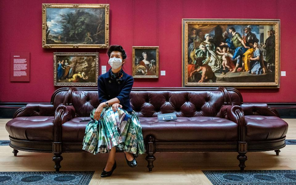 A woman wearing a face mask sits on a bench the National Gallery in London - VICKIE FLORES/EPA-EFE/Shutterstock