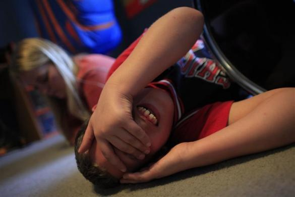 Parker Roos, who suffers from Fragile X, rolls around on the floor after getting into an argument with his sister as his mother Holly looks on at their home in Canton, Illinois, April 4, 2012. Fragile X is the most common known genetic cause of autism.