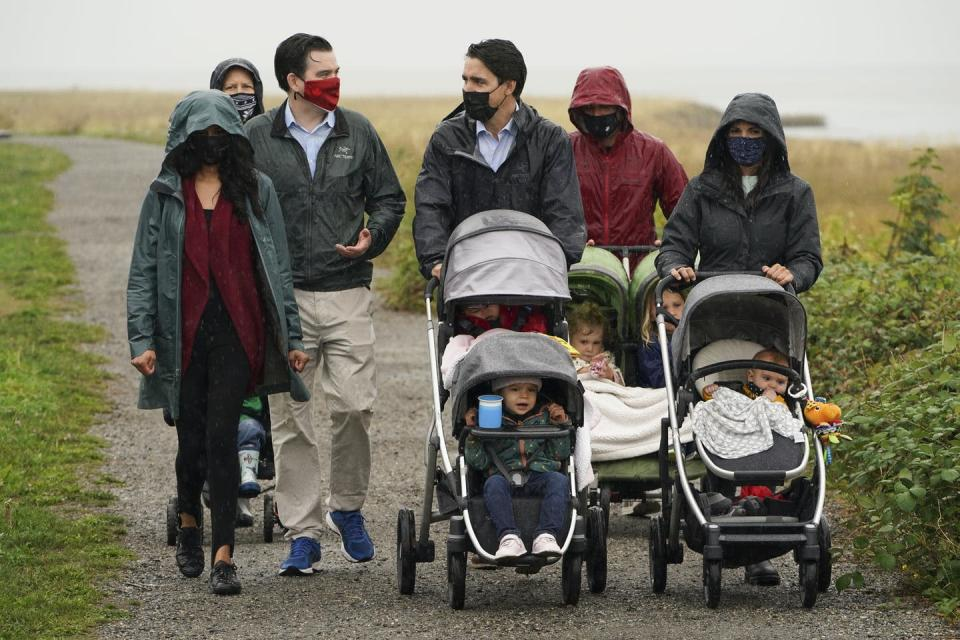 Trudeau pushes a stroller as he walks with families, including two women pushing strollers.