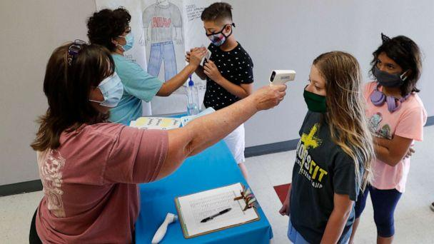 PHOTO: Amid concerns of the spread of COVID-19, science teachers Ann Darby, left, and Rosa Herrera check-in students before a summer STEM camp at Wylie High School, July 14, 2020, in Wylie, Texas. (L.M. Otero/AP)