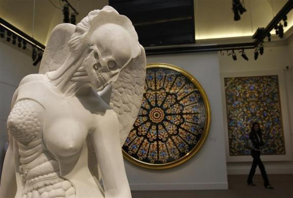 "A visitor walks behind ""Anatomy of an Angel"" by Damien Hirst during a preview of an upcoming auction of his work ""Beautiful Inside My Head Forever"" at Sotheby's in London September 8, 2008."