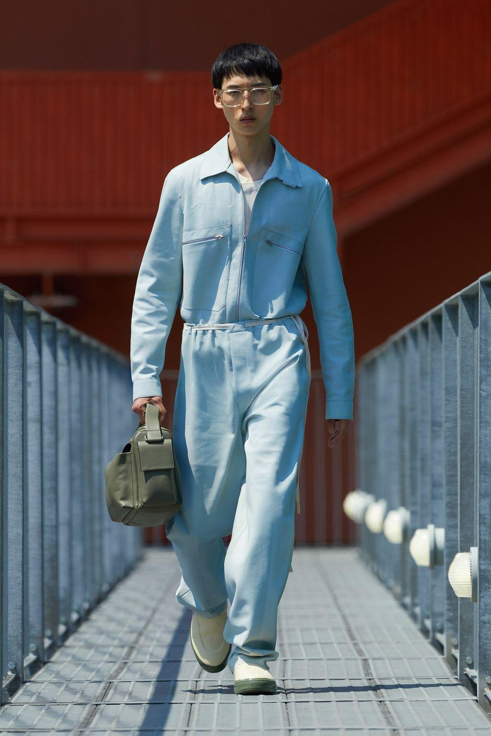<p>Can I pull off a jumpsuit? It's a question that I've been asking myself for years (only the biggest existential quandaries here at Esquire). I have always leant towards a big emphatic NO, but Zegna has reignited the spark! This baby blue, string-cinched piece is a bit Italian tailoring; a bit western with the pointed collar and chest pockets; a bit 'here to fix your waste disposal luv' with the tool bag. and more than a bit luxury toddler with all that volume and softness. Such is its commitment to craft that Zegna is building a new atelier in Novara, Piedemont, just to put out all the beautiful suits and outerwear that it has coming up. Yeah, yeah, I love all of that, but next summer I want to be the best dressed handyman/baby in Italy.</p><p><strong>FR</strong></p>