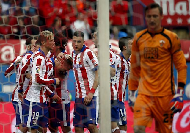 Atletico Madrid's Antoine Griezmann (3rd L, head down) is congratulated by teammates after scoring against Elche during their Spanish first division soccer match at Vicente Calderon stadium in Madrid, April 25, 2015. REUTERS/Susana Vera