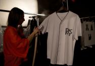 FILE PHOTO: A fashion assistant steams an item backstage before the DKNY London Collections: Men show in London