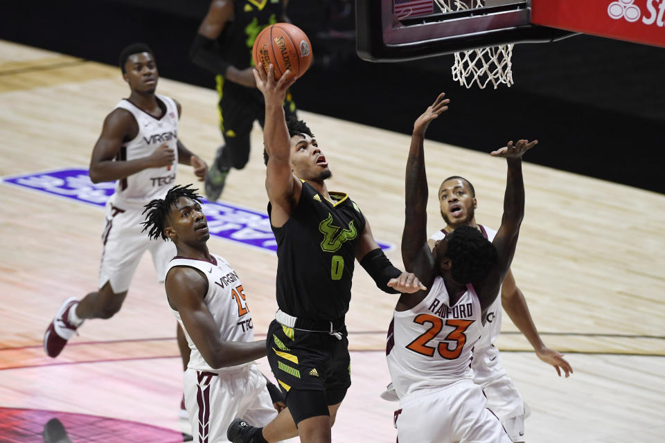 South Florida's David Collins goes to the basket as Virginia Tech's Jalen Cone, left, and Virginia Tech's Tyrece Radford, right, defend in the first half of an NCAA college basketball game, Sunday, Nov. 29, 2020, in Uncasville, Conn. (AP Photo/Jessica Hill)