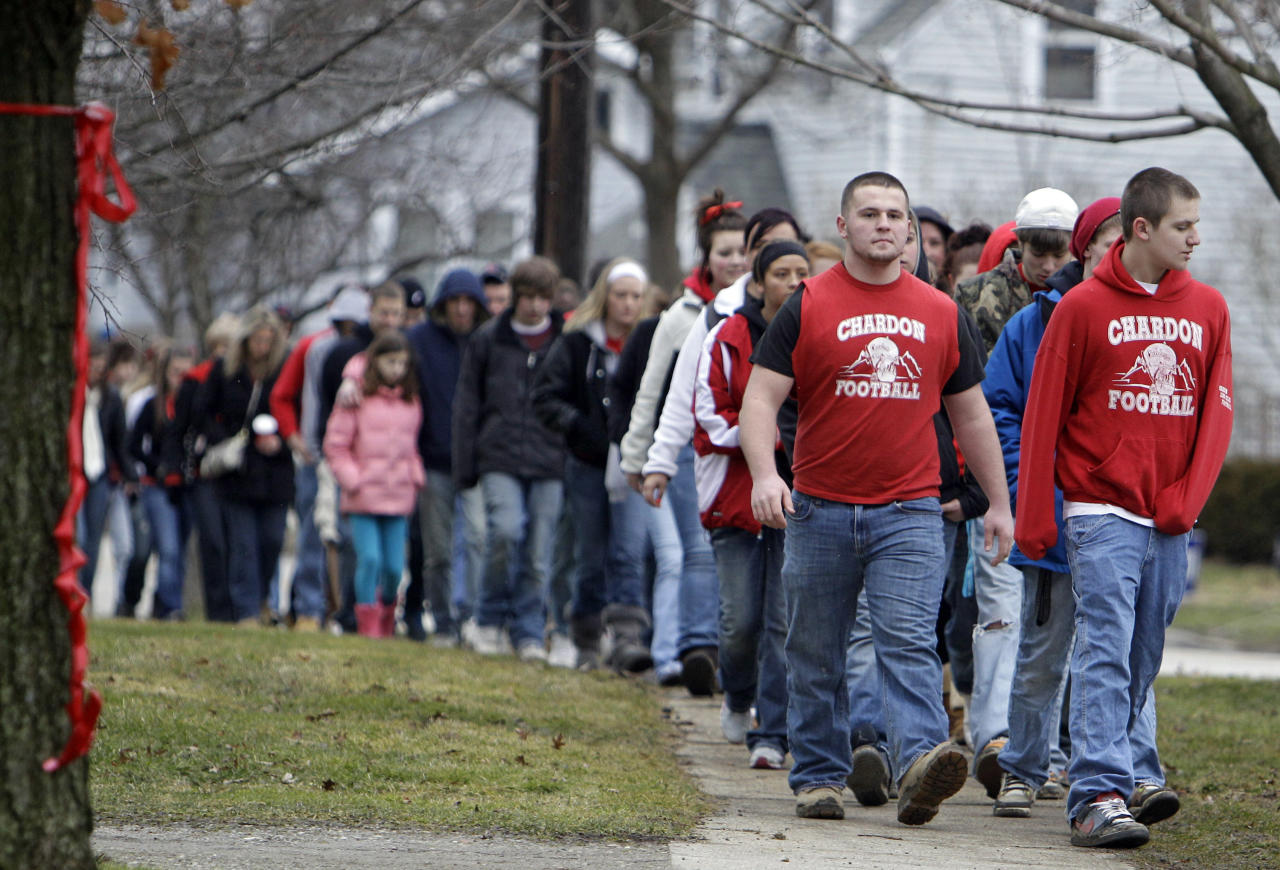 Hundreds of students and parents march to Chardon High School in Chardon, Ohio, Thursday, March 1, 2012, to honor the three students who were killed in a shooting there Monday. The school re-opened to parents and students Thursday and classes resume Friday. (AP Photo/Mark Duncan)