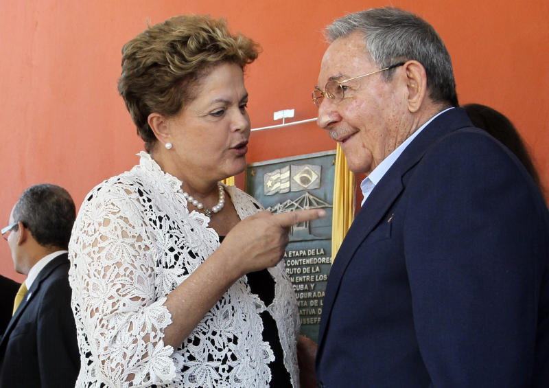 """Brazil's President Dilma Rousseff, left, and Cuba's President Raul Castro talk during the inauguration ceremony of the first phase of a port overhaul project in Mariel, Cuba, Monday, Jan. 27, 2014. The new port will be able to accommodate deeper-drafting """"post-Panamax"""" ships that will begin crossing the Panama Canal once an expansion project there is completed in the next year or so.(AP Photo/Ismael Francisco, Cubadebate)"""