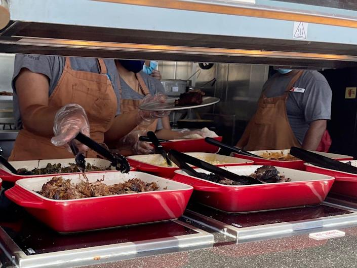 Crew members load meat onto a plate at Guy's Pig & Anchor Bar-B-Que Smokehouse.