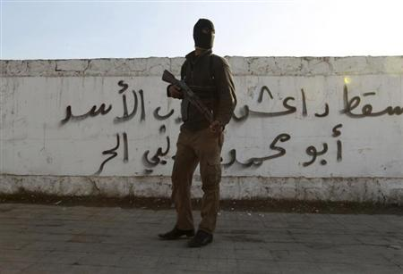 A Free Syrian Army fighter carries his weapon as he stands in front of graffiti in Aleppo