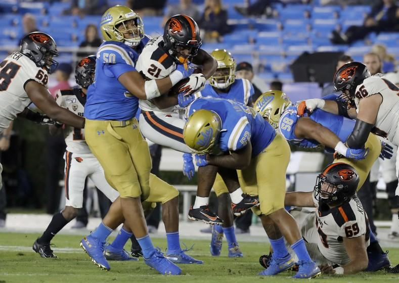 PASADENA,, CALIF. - OCT. 5, 2019. UCL:A defenders Tyler Manoa, left, and Winston Polite.