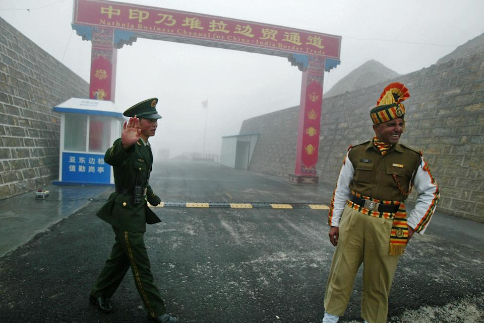 A Chinese soldier (L) and an Indian soldier stand guard at the Chinese side of the ancient Nathu La border crossing between India and China. (DIPTENDU DUTTA/AFP via Getty Images)