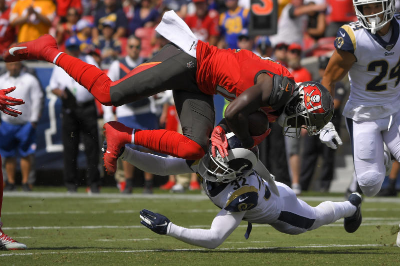 Tampa Bay Buccaneers wide receiver Chris Godwin, top, is tackled by Los Angeles Rams free safety Eric Weddle during the first of an NFL football game Sunday, Sept. 29, 2019, in Los Angeles. (AP Photo/Mark J. Terrill)