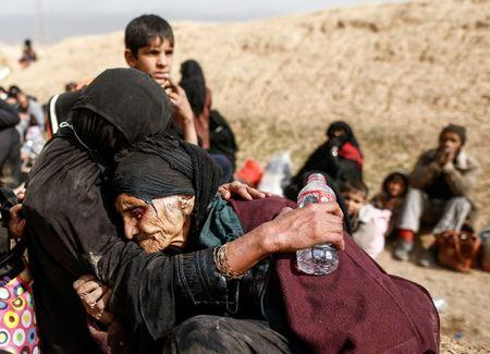 Khatla Ali Abdullah, 90, is embraced as she flees her home as Iraqi forces battle with Islamic State militants in western Mosul, Iraq February 27, 2017. REUTERS/Zohra Bensemra