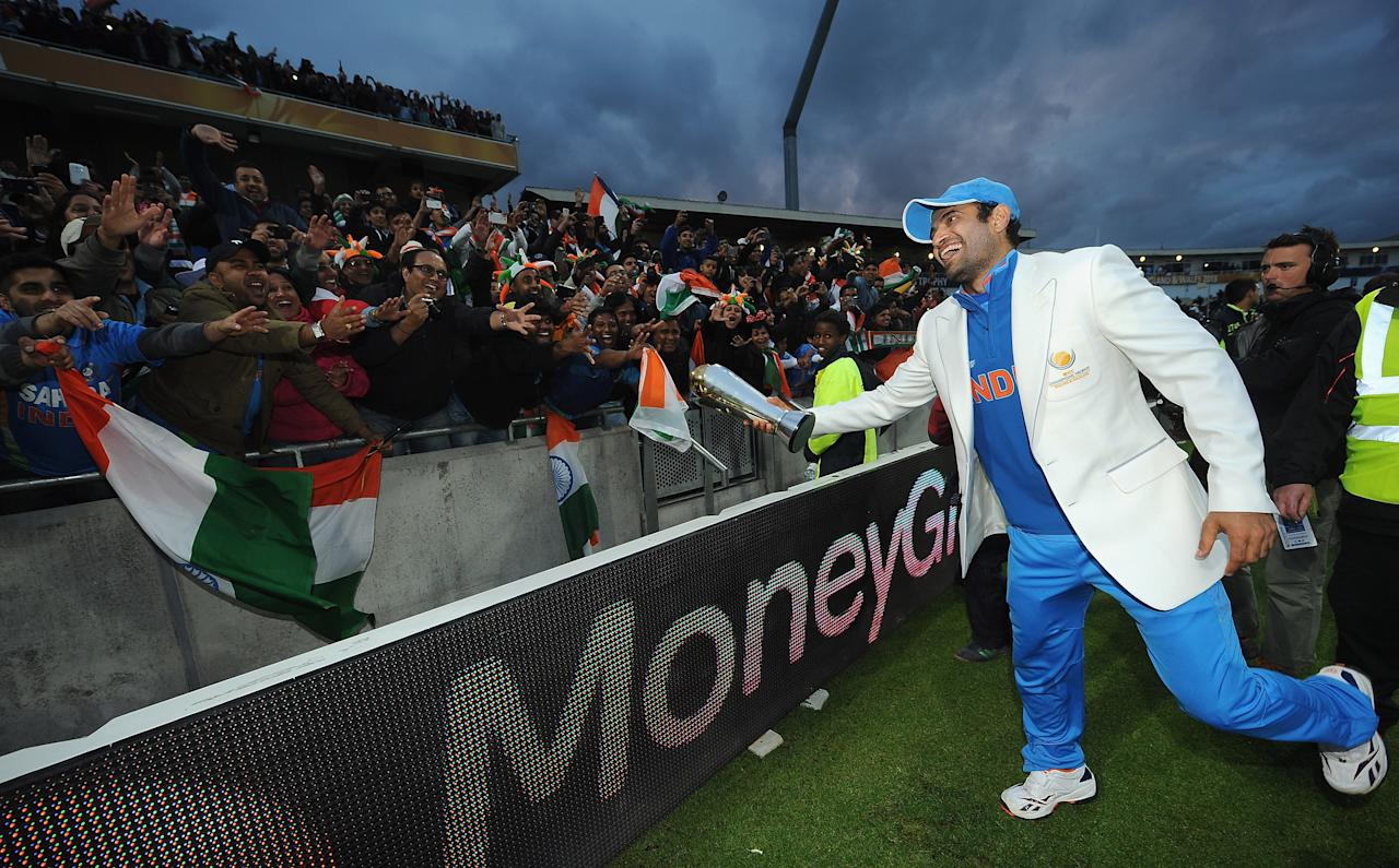 BIRMINGHAM, ENGLAND - JUNE 23:  Irfan Pathan of India plays with the crowd as he pretends to hand them the trophy as he celebrates victory with the Champions Trophy during the ICC Champions Trophy Final match between England and India at Edgbaston on June 23, 2013 in Birmingham, England.  (Photo by Christopher Lee-ICC/ICC via Getty Images)