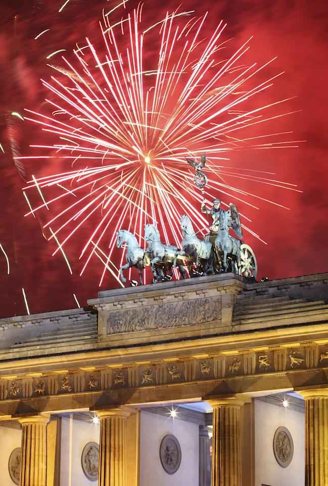 BERLIN, GERMANY - JANUARY 01:  Fireworks explode over the Quadriga statue atop the Brandenburg Gate on New Year's Eve on January 1, 2012 in Berlin, Germany. According to the media, up to one million people celebrate the country's biggest New Year's Eve Party.  (Photo by Andreas Rentz/Getty Images)