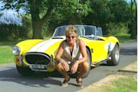 <p>With outfits like this—a vest and shorts—it's easy to forget Rod Stewart was one of the coolest people alive in the '60s and '70s. Thankfully, the singer's outfit is hidden as he squats down to showcase his car. </p>