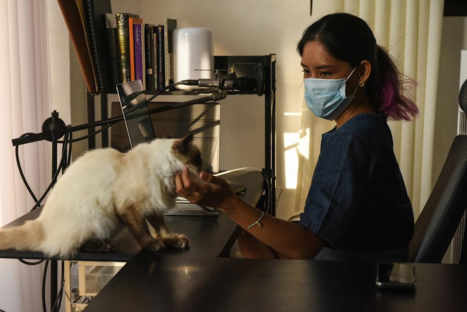 This photo taken on June 1, 2021 shows Tanya Mariano with her pet cat at her apartment in the town of San Juan, La Union province, north of Manila. Many digital workers in congested Manila, fearing COVID-19 and fed up with lockdowns and restrictions, are escaping to largely deserted nature hotspots to do their jobs – injecting much-needed money into communities dependent on outside visitors. (Photo: MARIA TAN/AFP via Getty Images)