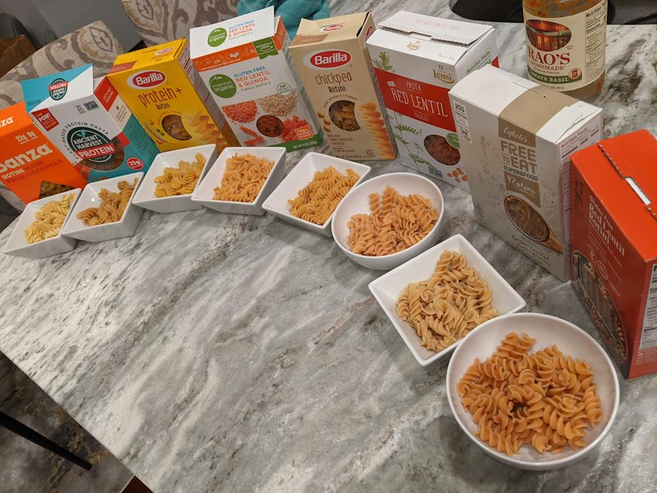 all 8 of the protein pasta brands lined up in a semi-circle on a kitchen counter