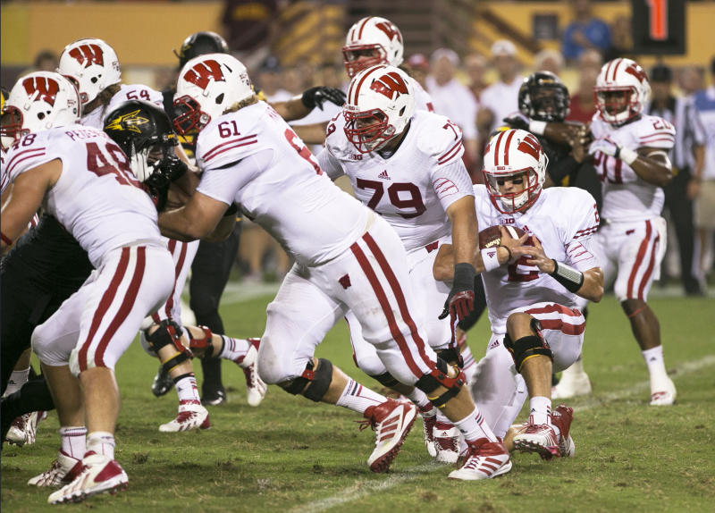 In this photo taken Saturday, Sept. 14, 2013, Wisconsin quarterback Joel Stave takes a knee after a 2-yard rushing loss late in the fourth quarter of their 32-30 loss to Arizona State in an NCAA college football game in Tempe, Ariz. The Pac-12 said, Monday, Sept. 16, 2013, that the officials did not act with enough urgency or properly handle the end of game situation when Stave awkwardly took a knee and the clock ran out on the Badgers in the ensuing confusion. (AP Photo/The Arizona Republic, Rob Schumacher) MARICOPA COUNTY OUT; MAGS OUT; NO SALES